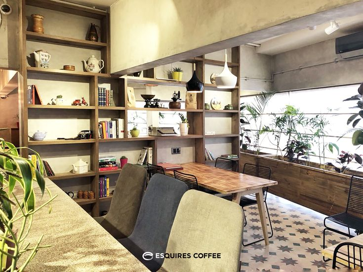 ESQUIRES COFFEE ZAMZAMA | KARACHI | PAKISTAN  _ Interior fitout _ Library wall #librarywall #bookshelf #bookcase #wood #seating #indoorseat #wirechair #woodentable #concretewall #planter #indoorplant #pakistanitiles #coffeeshop #coffeeshopkarachi #esquirescoffee #zamzama #karachi #pakistan