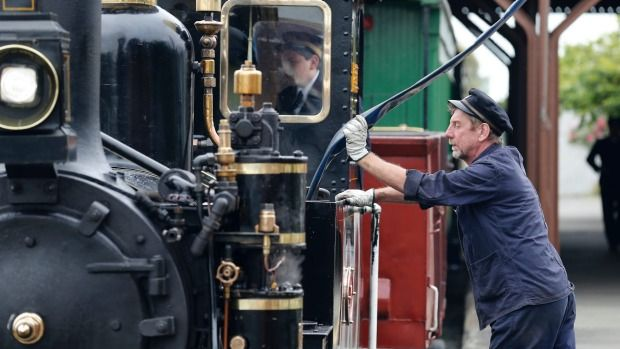Third generation steam train driver Bill Knight tops up the  Pleasant Point train with water.