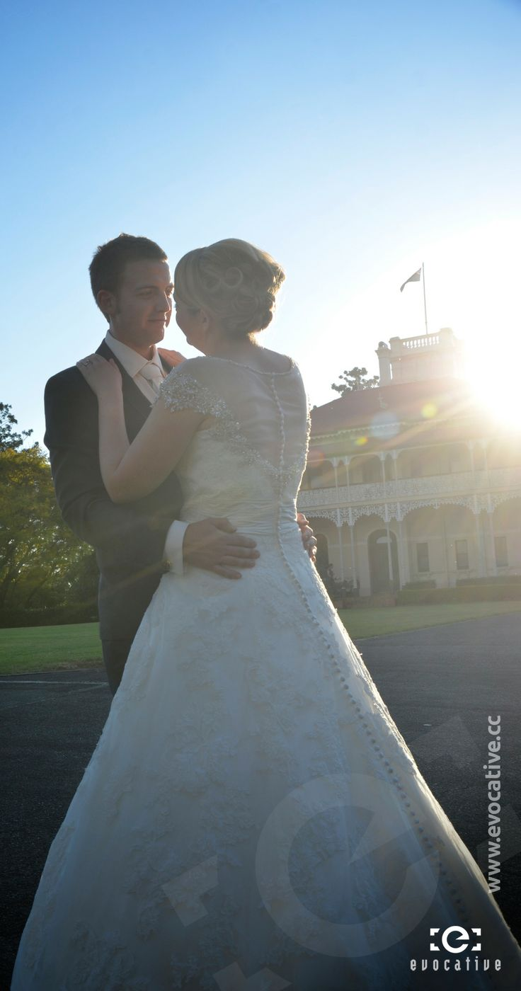 Bride and groom embracing in the afternoon sunlight, with the Woodlands of Marburg mansion in the background. #WeddingPhotography #LensFlare