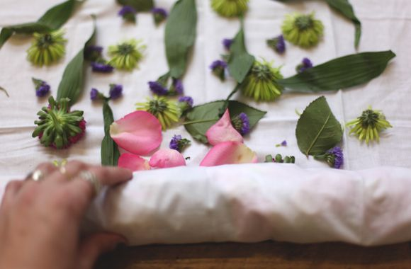 eco dyeing with flowers - lay petals and leaves on fabric, roll up using a stick, wrap bundle in twine, then steam