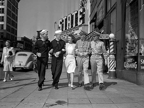 Two sailors and two soldiers walk down Hennepin Avenue in Minneapolis with a female companion.  Captured by an unknown Minneapolis Star Tribune photographer on July 8, 1942.