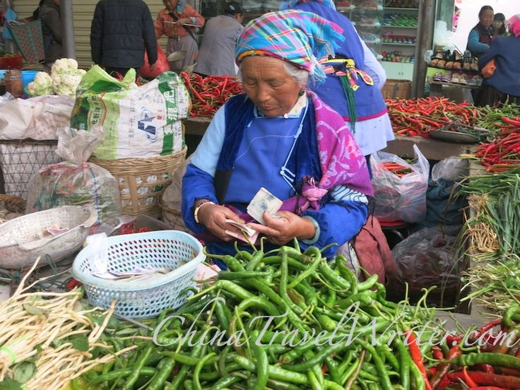 A woman vendor counts her money at the market.