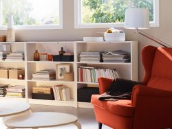 A basement living room with three low BILLY bookcases in white and a STRANDMON wing chair in orange