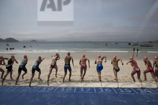 Competitors run to the water for the start of the women's triathlon event at the 2016 Summer Olympics in Rio de Janeiro, Brazil, Saturday, Aug. 20, 2016. (AP Photo/Felipe Dana)