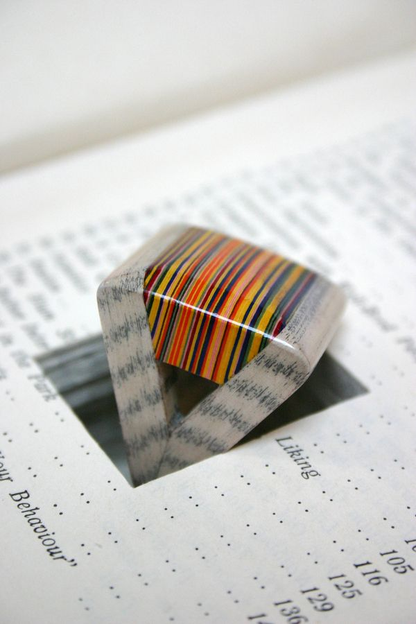 Jeremy May makes jewelry by carving shapes out of books and laminating them.
