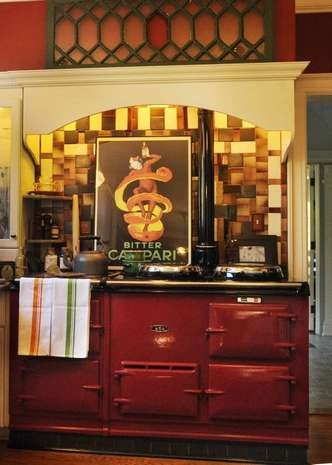 The AGA range is the centerpiece of this kitchen. Vintage tiles behind the AGA add a sense of dimension and color for the space.