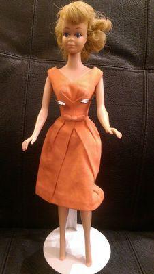 Here  is a beautiful 64 Midge wearing the Orange Belle Dress. Doll is  excellent. She has one very faint discoloration near her left ear. Lips  are coral pink, no, big baby blue eyes. Makeup is about 99%. Fingernail  polish is about 70% and toenail polish is about 70%. No neck splits or  nose nips. Fingers and toes are not nicked. Hair has been put in a  ponytail and original rubber band replaced with an orthodontic rubber  band. Marked Midge T.M./c1962/Barbie R/c1968/by/Mattel…
