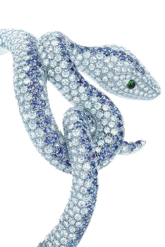 Tiffany artisans skillfully trace the serpent's sensuous curves with Montana sapphires and diamonds exquisitely set for an ombré effect, with two emerald cabochons. Bracelet of 18k white gold.