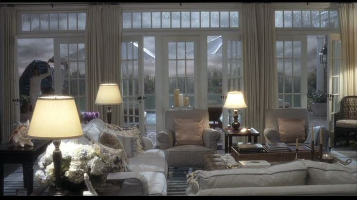 """The living room in """"As Good as it Gets""""...I love the windows looking out onto the beach, the soft pastels and the lamp lighting. I hope one day my home looks this safe when a storm is coming!"""