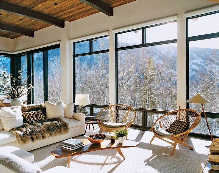 Aerin's Aerie - The light-filled living room features a Jean-Michel Frank sofa, Hans Wegner hoop chairs, luxurious fur throws, and exhilarating views over Aspen Mountain.