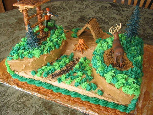 Deer Hunting Cake - I used a regular sheet cake and bake a round cake which I cut it in half and laid those on the ends of the sheet cake. I knew I wanted to do a tree stand, but didn't know quite how to do one so this is what it turned out to look like. The tent is made from graham crackers. My boy sure did love it!!
