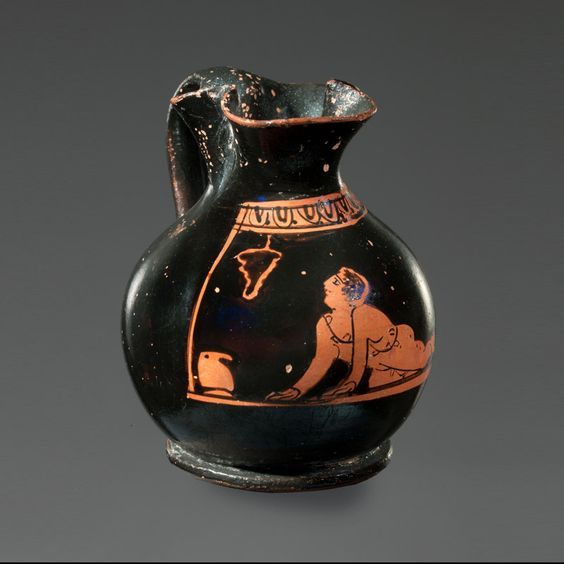 Greek red-figure miniature chous, 420-400 B.C. The choes were given as gifts to the 3 years old boys who used them for their first wine tasting.These rituals were taking place during the Anthesteria, the Athenian festival held every February. The scenes on these small jugs were closely related to the life of children: here the boy crawls to the left where lies a chous; he looks with admiration on a bunch of grapes that symbolize Dionysos, the god of the vine, 6.2 cm. Private collection