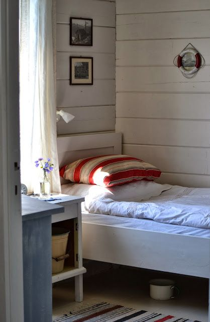 A simple nautical look with clean white linens and a striped red pillow.
