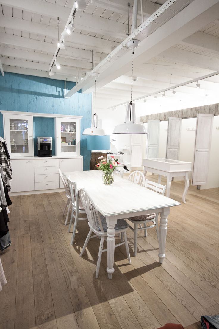 New shop interior in pastel colors en brocante style: white table en different chairs