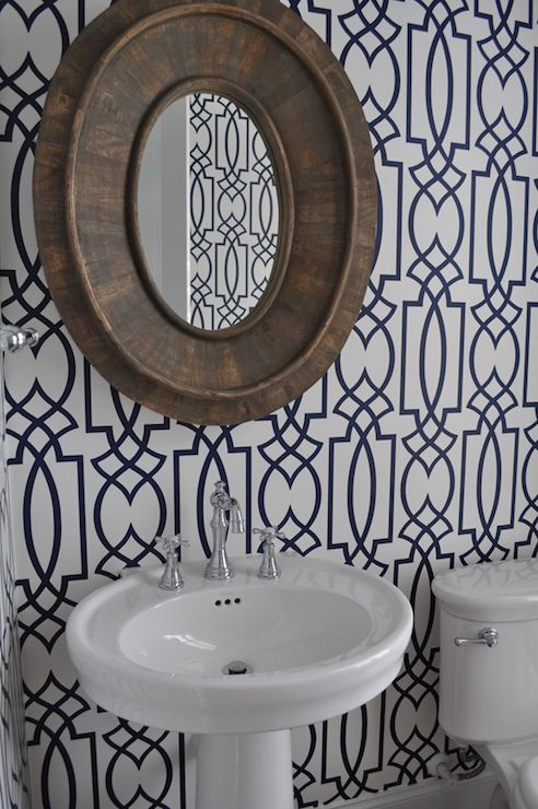 Chic powder room with walls papered in Antonina Vella Dolce Vita Wallpaper in Navy Blue adorned with a Restoration Hardware Pieced Oval Mirror hung above an oval pedestal sink with hook spout faucet.
