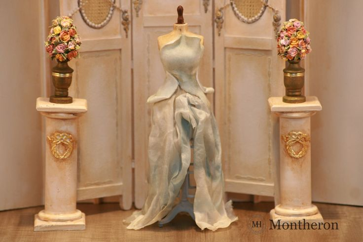 Miniature mannequin dressed in a blue  evening gown.