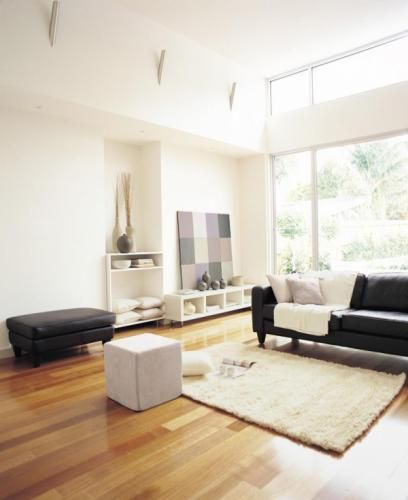 White Walls With Black Furnishings And Natural Honey Coloured Floor Boards