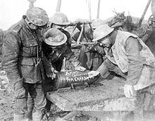 WW1 - Canadian artillerymen add an early seasonal message to a shell for their 60 pounder field gun on the Somme front.