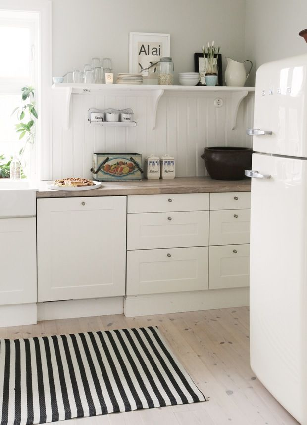 Perfection with the stripy rug, retro fridge, wood countertops, + white drawers.