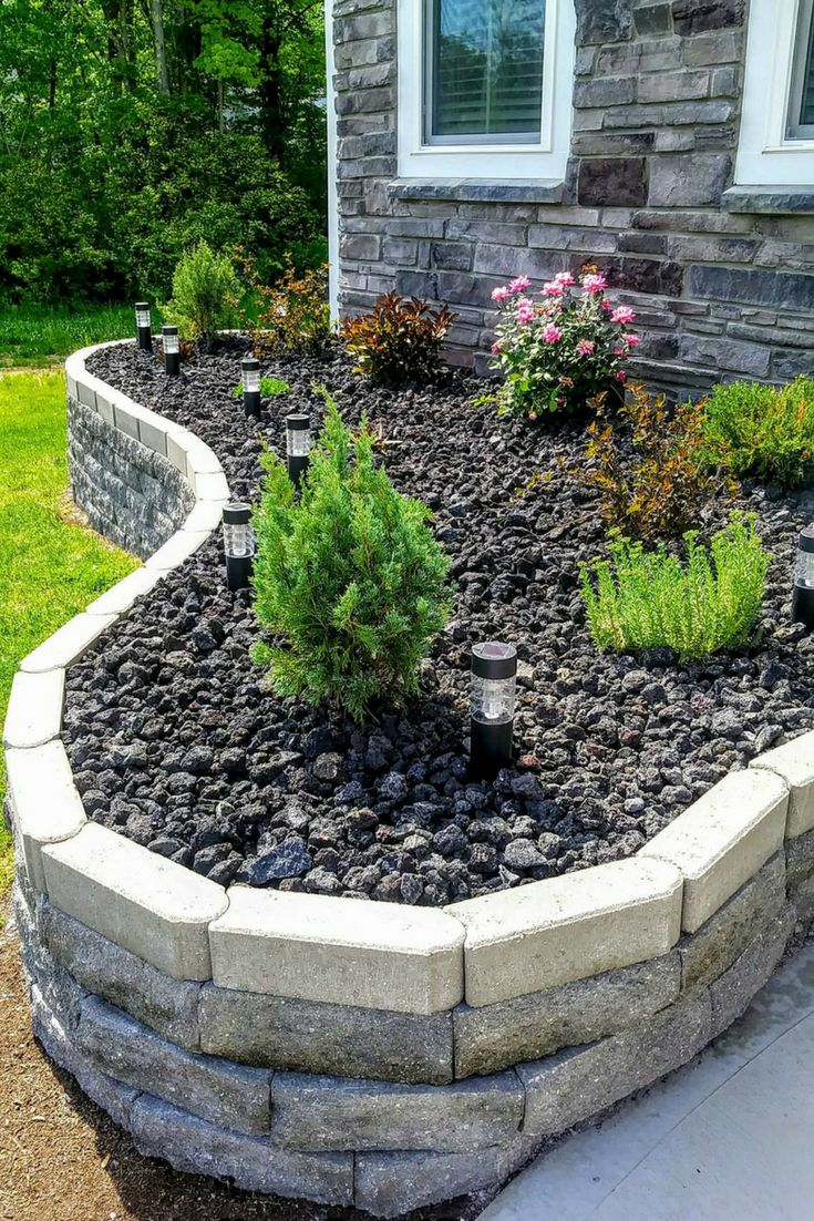 flower bed idea with black lava rock and retaining wall. Black Bedroom Furniture Sets. Home Design Ideas