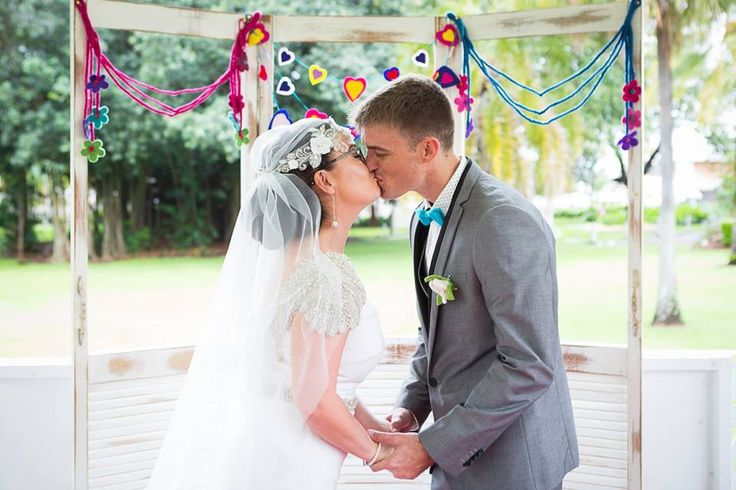 Vintage ceremony backdrop draped with colourful felt flower garland