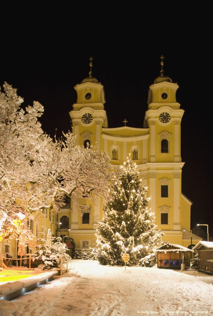 Austria, Salzkammergut, Mondsee, View of church and christmas tree in christmas market at night