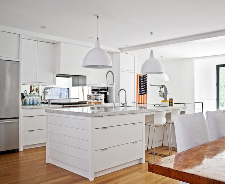 Sleek White Kitchen Features Flat Front Cabinets Paired With Marble Countertops And A Mirrored Backsplash