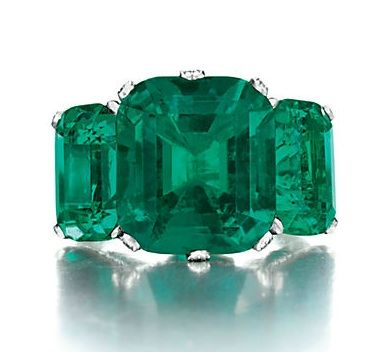 Set with a cushion-cut emerald, weighing approximately 8.51 carats, flanked on either side by two smaller cushion-cut emeralds, weighing approximately 4.04 and 3.94 carats, to the single-cut diamond shoulders, mounted in platinum