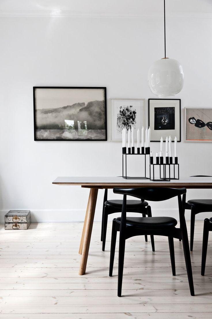 Sorte stoler, tre bord. Bildene på bakveggen.