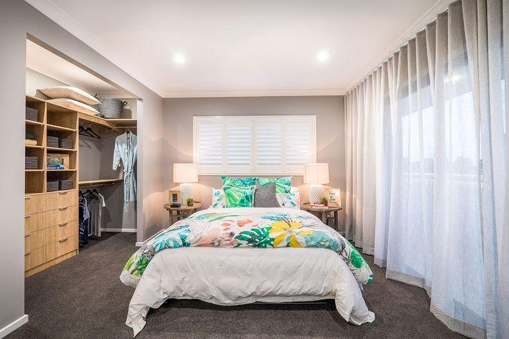 Tropical master bedroom. Main bedroom. Walk-in robe. Tropical bedspread. Grey curtain drapes.