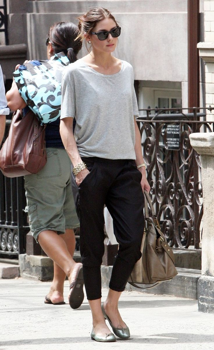 Olivia Palermo Casual look, a dark ankle trouser with a pair of silver flats and an oversized grey tee. Throw your hair up in a bun and a cute sunny to go with your satchel bag to carry your look off.