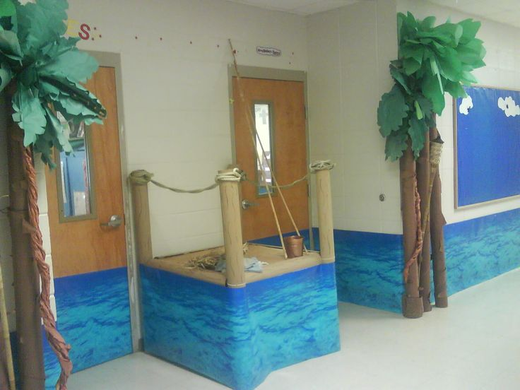 ocean or water classroom door decoration, boat dock is made with carpet rolls and rope added cane poles and bucket of plastic worms cane poles and trees made out of carpet rolls