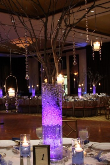 Branch centerpieces hang glitzy crystals and candles from