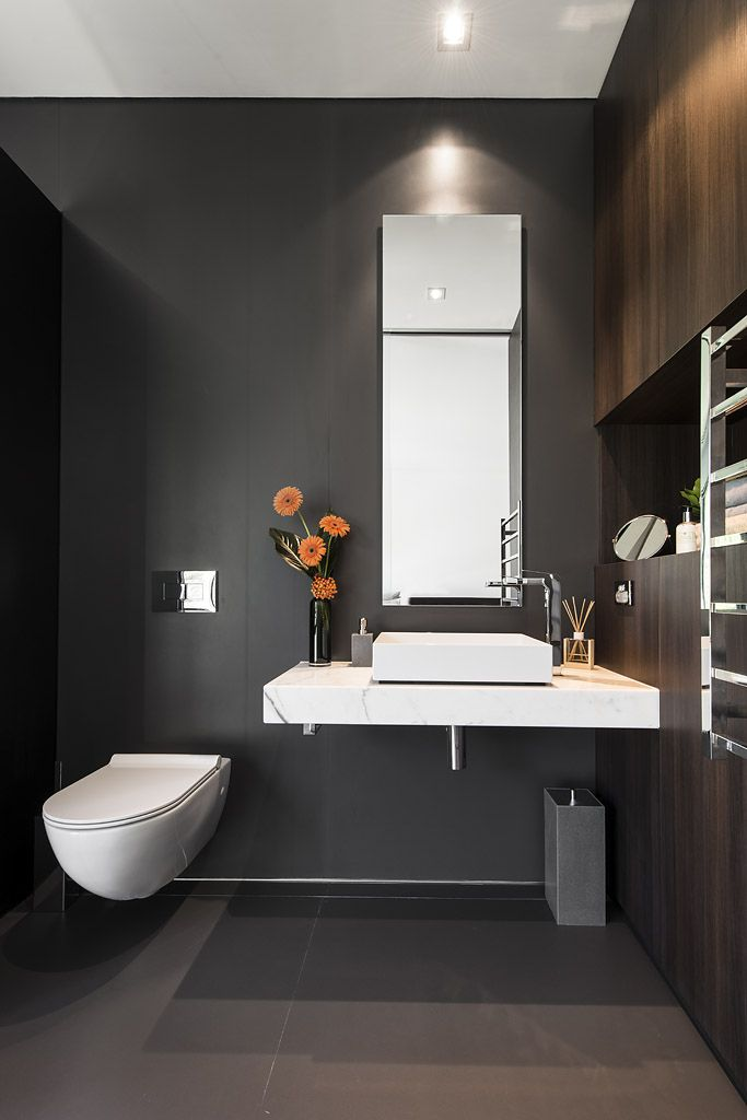 Simple, clean lines with integrated custom built cabinetry and floor to ceiling tiles make for a dramatic bathroom by Urbane Projects, Perth.