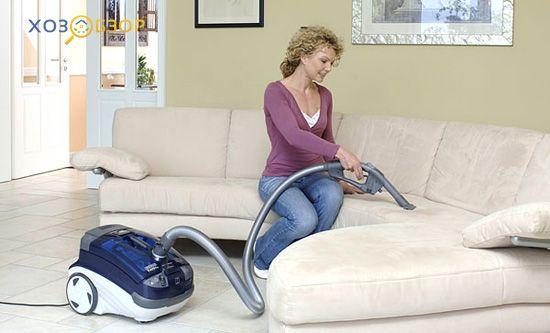 женщина пылесосит диван