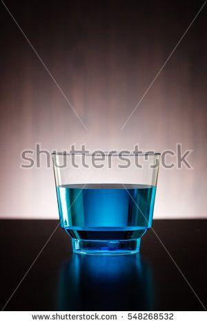 Vertical blue drink in a glass. alcohol, bar, beverage, black, blue, chemistry, color, drink, fluid, food, glass, light, liquid, one, plastic, restaurant, table, transparent, water, wood