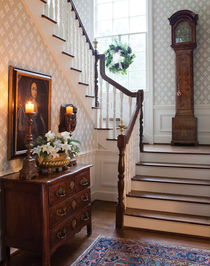 A silver container filled with alabaster lilies and evergreen sprigs and a woodland-inspired wreath at the window complement the stately antiques and furnishings of the foyer.