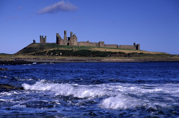 Dunstanburgh Castle lies on a spectacular headland on the coast of Northumberland in northern England, between the villages of Craster and Embleton. The castle is the largest in Northumberland and the site shows traces of much earlier occupation before the erection of the castle was started in 1313 by the Earl of Lancaster.