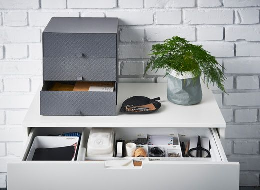 The top of a dresser by an entrance with a dish for keys, drawers to sort mail and an organized drawer insert with compartments.