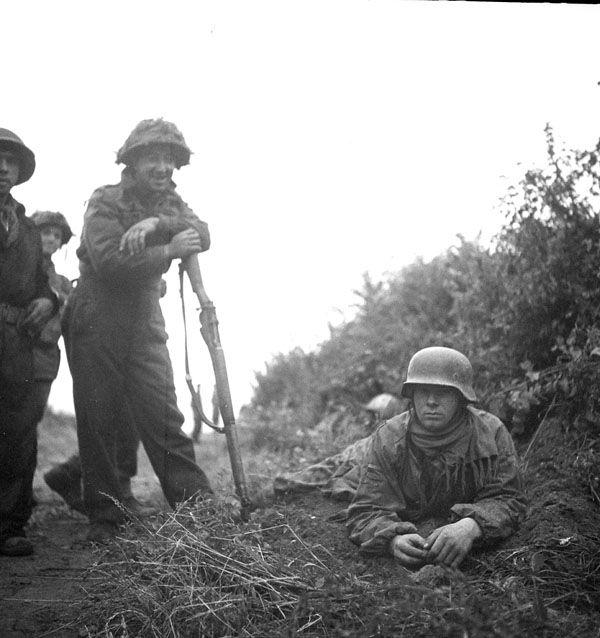 Private Leopold Marcoux of Le Régiment de la Chaudière with a German prisoner, Carpiquet, 4 July 1944.
