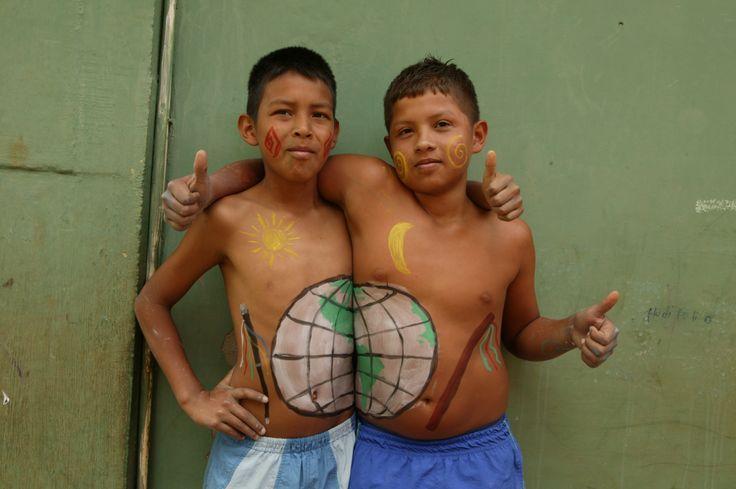 """Colombia - Jhon (12) en Santiago (12) houden van schilderen. Het liefst laten ze iets zien van hun volk,  Nasa. De Nasa hebben een eigen taal en cultuur. Van het geweld om hen heen moeten ze niets hebben. Jhon (links): """"De stok op onze buik is de vredesstaf  van de indiaanse vredeswacht. Samen delen we de wereld, maar mijn helft is ietsje groter, haha."""" Santiago: """"De ronde krul op mijn wang is ons symbool voor leven.""""  Jhon: """"Het figuurtje op mijn wang betekent: familie en macht."""""""