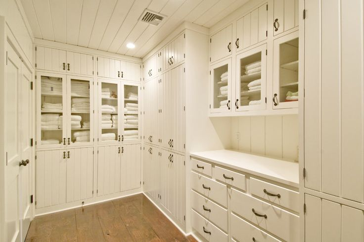 Linen closet features tongue and groove ceiling over floor to ceiling built-in cabinets with beadboard doors adjacent to glass-front linen cabinets atop rustic floors.