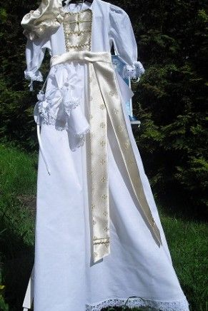 Dåpskjolen Edelveis er en lang, foret dåpskjole i hvit lin. Kristnesmekken på denne dåpskjolen kommer med forstykke og lindebånd i brokade/gull. Leveres med fôret brokadelue, spisesmekke og krage i lin, samt smokkepompadur.