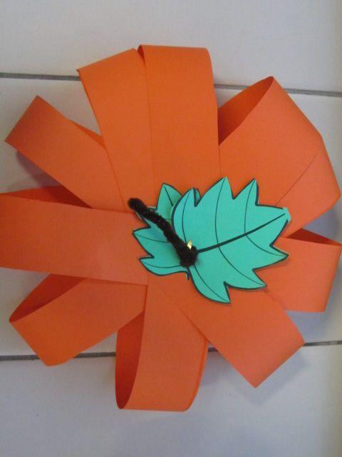 Pompoen Oranje stroken op elkaar leggen. Onder en boven een splitpen. Dan uit elkaar trekken. Boven een blaadje en stokje vastmaken en klaar!