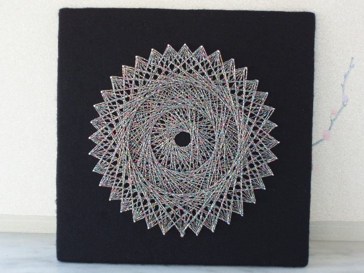 This is my fifteenth piece of string art, the second one I made today, with multicoloured metallic threads interwoven around silver thread. Enough circles for now, methinks, time to move on to more ambitious projects over the summer.