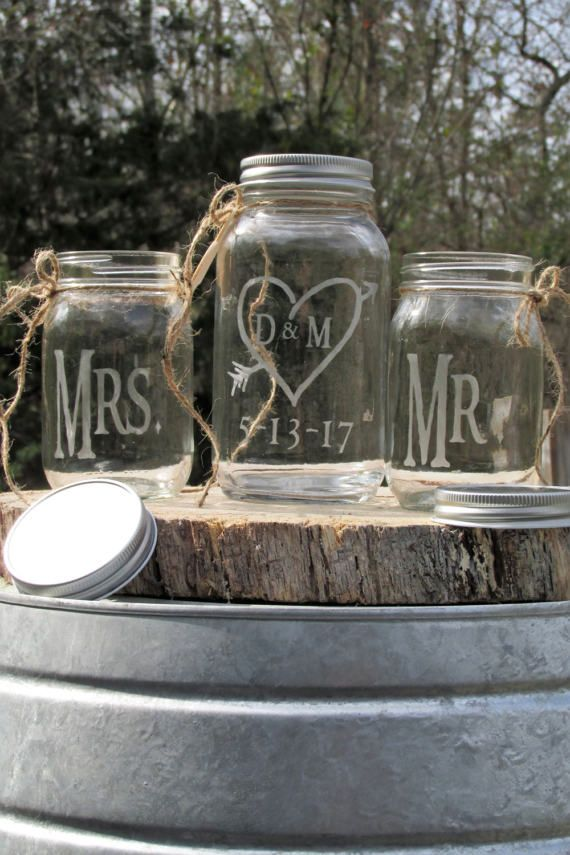 Arrow Pierced Heart Initials Personalized Mason Jars Unity Sand Set Mr. Mrs. Sand Ceremony Set - Perfect for any country, barn, rustic or any Traditional Themed Wedding.  Included in this set: One Brides Glass Etched in a Rustic Font Mrs. One Groom Glass Etched in a Rustic Font Mr. Both are about 5 Tall and hold about 1 1/2 pounds of sand. Individual Glasses can be used in ceremony, and once washed out, they can also be used as toasting glasses at the reception.  One Unity Glass that is ...