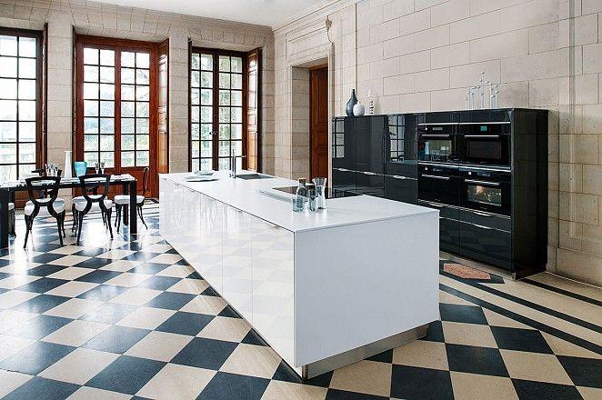 Ruim wit kookeiland met zwart hoogglans kastenwand die ruimte biedt aan diverse apparatuur.