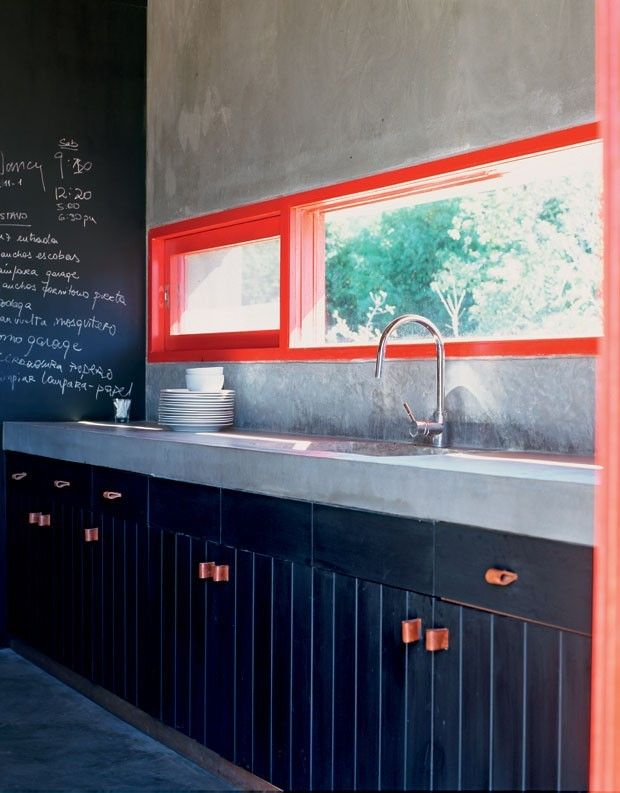 Garzon, Uruguay house sports painted black cabinetry with rough hew leather draw pulls. #remodelista