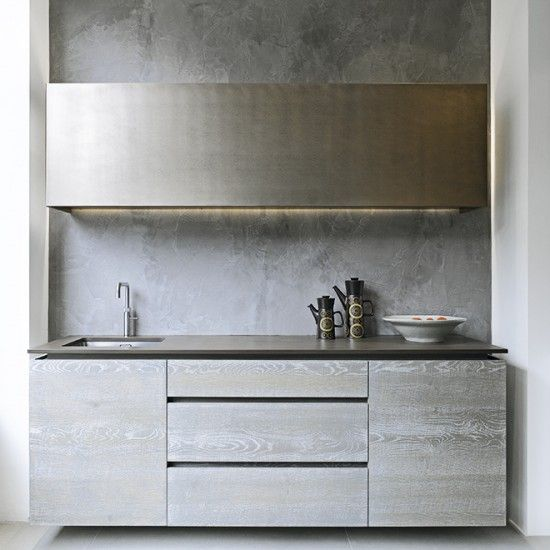 Perfect for modern and industrial schemes, the burnished beauty of Venetian polished plaster lends a cool urban feel, paired with the sleek handleless units in a complementing grey wash.