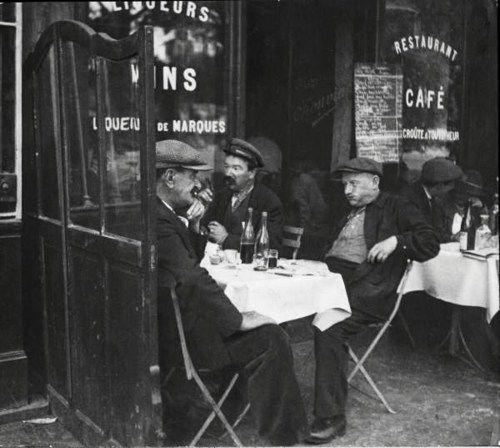 Men enjoying a bottle of wine at a cafe. Paris, 1920s.